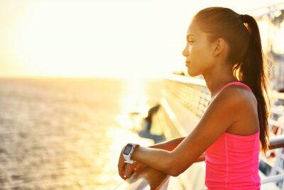Affisch Aktiv kvinna avkopplande efter köras på kryssningsfartyg tittar på havet under sommarlovet. Asiatisk löpare flicka klädd Smartwatch pulsAktivitetsKontroll leva en hälsosam livsstil.