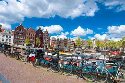 Affisch Amsterdam, Nederländerna april 27: Traditionell Amsterdam stadsbild med medival hus, cyklar på bryggan april 27,2015. Amsterdam är den folkrikaste staden i Nederländerna.