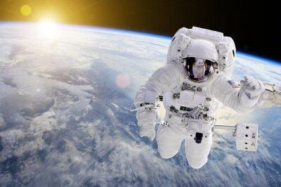 Affisch Astronaut i rymden, i bakgrunden vår jord ett solen - Delar av bilden som tillhandahålls av NASA