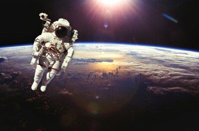 Affisch Astronaut i rymden ovanför jorden under solnedgången. element