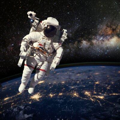 Affisch Astronaut i yttre rymden ovanför jorden nattetid. Elem