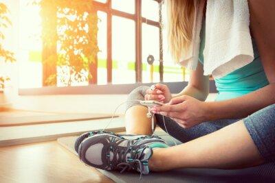Affisch Attraktiv blond kvinna med smart telefon, vila efter gym träning