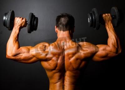 Affisch bakifrån av kroppsbyggare träning med hantlar på svart bakgrund