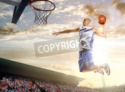 Affisch Basketspelare i handling på bakgrund av himmel och publiken
