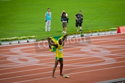 Affisch Beijing - 16 augusti: Usain Bolt firar håller den jamaicanska flaggan efter att ny värld 100 meter rekord för män