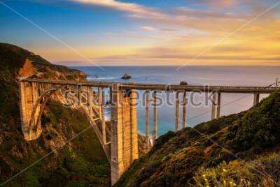 Affisch Bixby Bridge (Rocky Creek Bridge) och Pacific Coast Highway vid solnedgången nära Big Sur i Kalifornien, USA. Lång exponering.