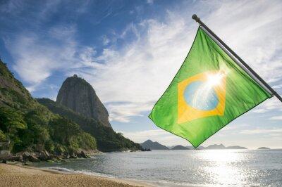 Affisch Brasilianska flaggan vid Praia Vermelha Röda stranden med en soluppgång utsikt över Sockertoppen Pao de Acucar i Rio de Janeiro Brasilien