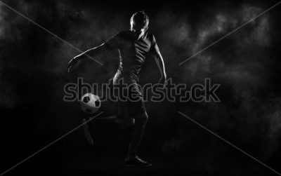 Affisch bright soccer playerl on the black background