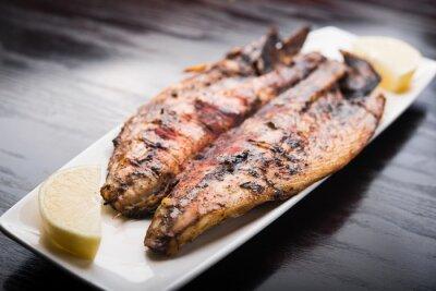 Affisch Fisk på grillen med citron på vit platta