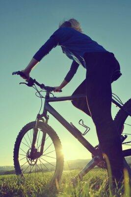 Affisch Flicka på en cykel i solnedgång