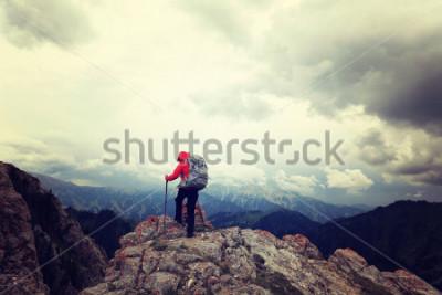 Affisch framgångsrik kvinna backpacker njuta av utsikten över bergstoppen