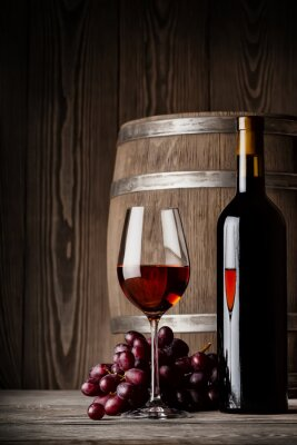 Affisch Glas rött vin med flaska och fat stående