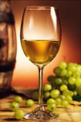 Affisch Glas vitt vin framför gröna druvor och gamla fat