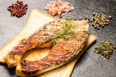 Affisch grillad laxfilé över varma bröd skiva och kryddor över skiffer