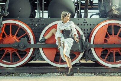 Affisch Kvinna i vintageklänning sitter på lokets hjul.