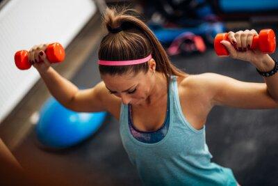 Affisch Kvinna lyft vikter och arbetar på axlarna på gymmet