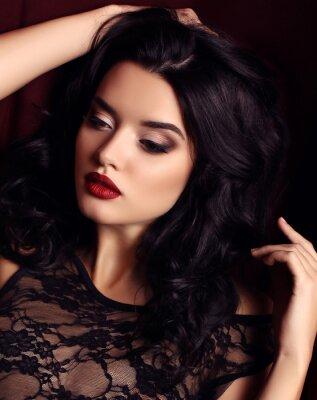 Affisch kvinna med mörkt hår och kvällsmakeup, bär lyxig svart spetsklänning