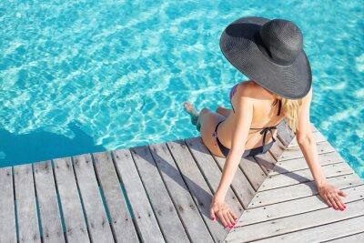 Affisch Kvinna som sitter på däck vid poolen