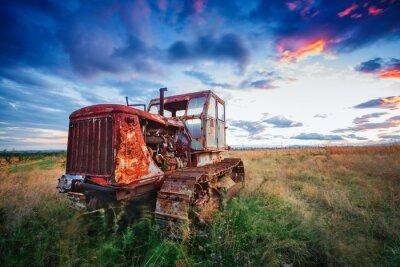 Affisch ld rostig traktor i ett fält på solnedgång