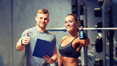 Affisch leende ung kvinna med personlig tränare i gymmet