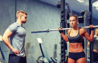 Affisch man och kvinna med skivstång böja musklerna i gymmet