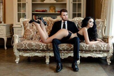 Affisch Mode foto romantik av sexiga älskare par. kvinna med svart lockigt hår i svart underkläder och man bär kostym