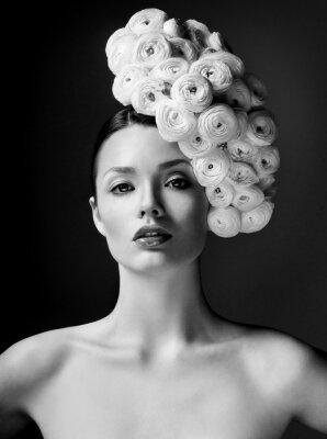 Affisch modell med stor frisyr och blommor i håret.