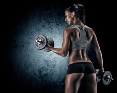 Affisch Muskulös kvinna i studion på mörk bakgrund