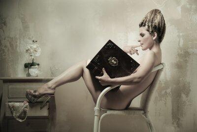 Affisch Naken kvinna som sitter i en stol läser en bok inomhus