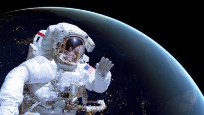 Affisch Närbild av en astronaut i rymden, jorden natten i bakgrunden. Delar av denna bild är inredda av NASA