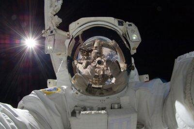 Affisch närbild av flytande astronaut med en återspegling av rymdstation visar (vissa delar artighet av NASA)