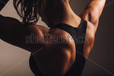 Affisch Närbild skott av ryggen av kvinnlig fitnessmodell. Ung kvinna i sportkläder med muskulös kropp.