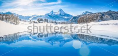 Affisch Panoramautsikt över vackra vita vinterlandskapet landskap i Alperna med snöiga bergstoppar som reflekterar i kristallklart bergsjö på en kall solig dag med blå himmel och moln