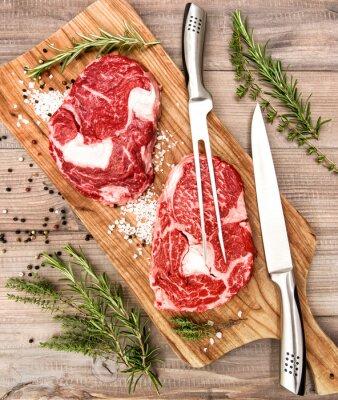 Affisch Rå färskt kött Ribeye biff med örter och kryddor på trä skrivbord