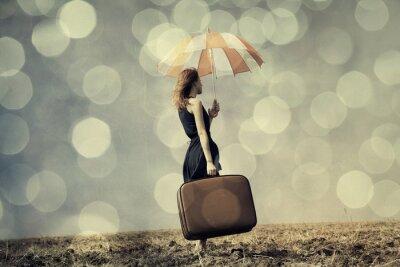 Affisch Redhead flicka med paraply och resväska på blåsiga fältet