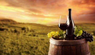 Affisch Rött vin flaska och glas på wodden fat
