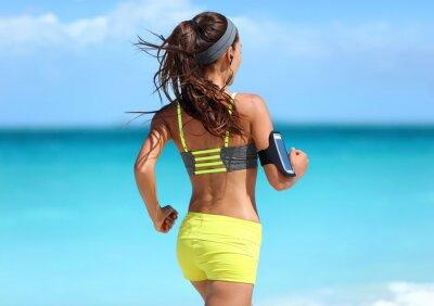 Affisch Running motivation - löpare utbildning med musik sedd bakifrån jogging i mode gul remmar sport-bh och neon shorts kläder bär trådlösa hörlurar på sommar strand bakgrund.