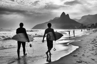 Affisch Scenic svartvit bild av Rio de Janeiro, Brasilien med brasilianska surfare promenad längs stranden Ipanema Beach