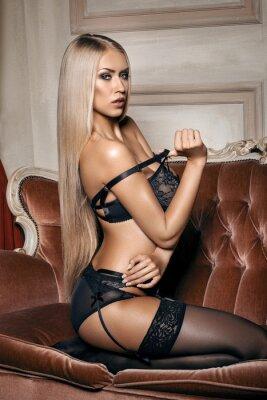 Affisch sexig kvinna i förförisk svart underkläder sitter på en soffa i strumpor