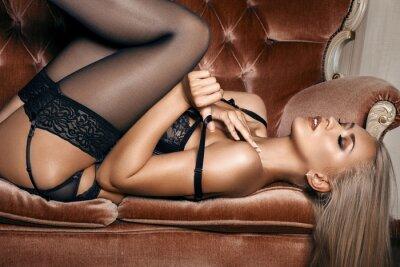 Affisch sexig kvinna i förförisk svart underkläder som ligger på en soffa i strumpor