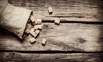 Affisch Socker från sockerrör raffinerade i påsen. På trä bakgrund.