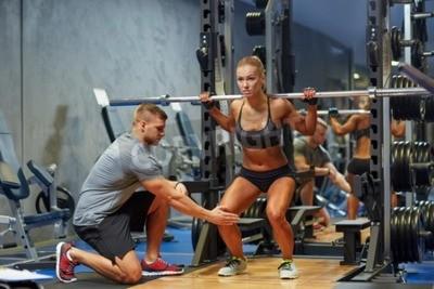 Affisch sport, fitness, lagarbete, bodybuilding och människor koncept - ung kvinna och personlig tränare med skivstång böja musklerna i gymmet