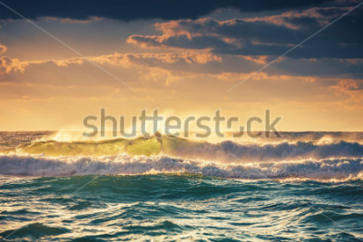 Affisch Sunrise and shining waves in ocean