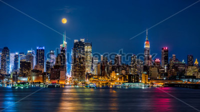 Affisch Super Moon above New York skyline. The top of the Empire State Building is illuminated with the colors of the German and Argentinian flags in honor of the Soccer World Cup final.