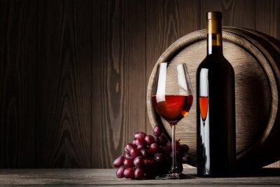 Affisch Svart flaska och glas rött vin med druvor och fat