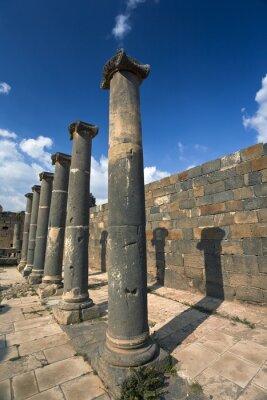 Affisch Syrien. Bosra. Resterna av de romerska baden - basaltpelare. Denna webbplats är på Unescos världsarvslista
