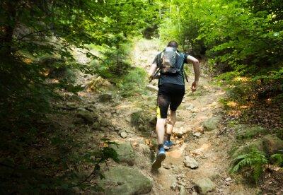 Affisch Trail Runner med ryggsäck kör upp branta backen