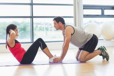 Affisch Tränare hjälpa kvinnan att göra buken crunches i gym