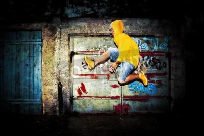 Affisch Ung man hoppar / dans på grunge graffiti vägg bakgrund