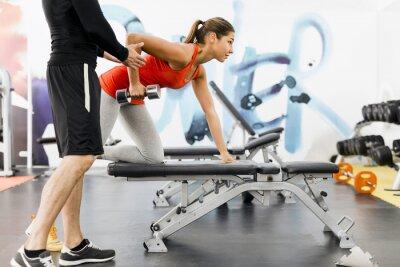 Affisch Ung manlig tränare att ge instruktioner till en kvinna i ett gym